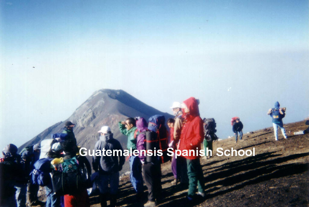 Group of tourists on the Acatenango summit, in the rear is the Fuego volcano.